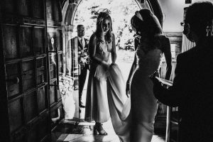 Black and White photo of Sarah arriving for her wedding ceremony at Jesmond Dene House. Sarah wears Petunia wedding dress by Suzanne Neville, at her Jesmond Dene House wedding in Newcastle England