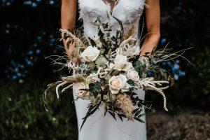 Real bride Sarah and her stunning wedding flower bouquet, wears Petunia wedding dress by Suzanne Neville, at her Jesmond Dene House wedding in Newcastle England